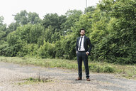 Businessman standing in remote landscape - UUF14075