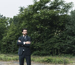 Businessman standing in remote landscape - UUF14078