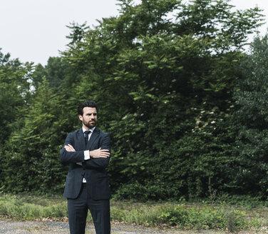 Businessman standing in remote landscape - UUF14078