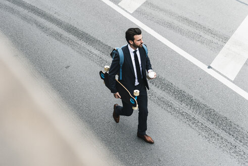 Businessman with takeaway coffee and skateboard walking on the street - UUF14084