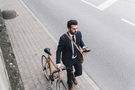 Businessman with bicycle and cell phone walking at the street - UUF14093