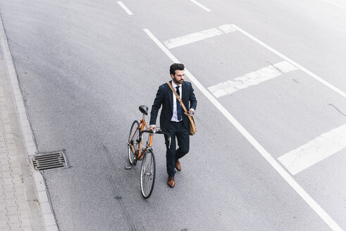 Businessman with bicycle and cell phone walking on the street - UUF14096