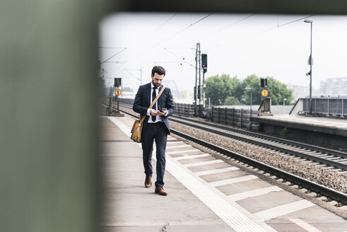 Businessman with cell phone walking at the platform - UUF14105