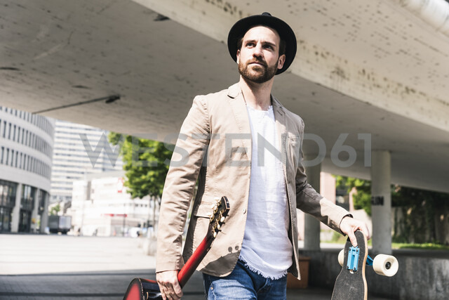Young man with guitar and skateboard walking in the city - UUF14123