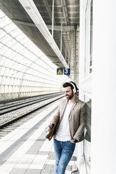 Young man wearing headphones waiting at the station platform - UUF14129