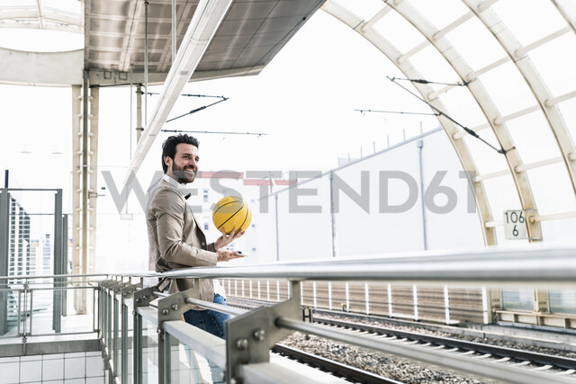 Smiling young man with cell phone and basketball at the station platform - UUF14135