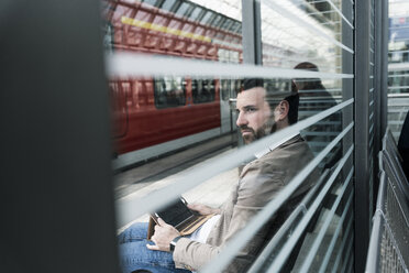 Young man with tablet waiting at the station platform - UUF14141