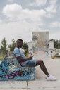 Young man in skatepark sitting on bench, listening music - ACPF00012