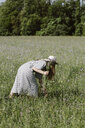 Italy, Veneto, Young woman plucking flowers and herbs in field - ALBF00402