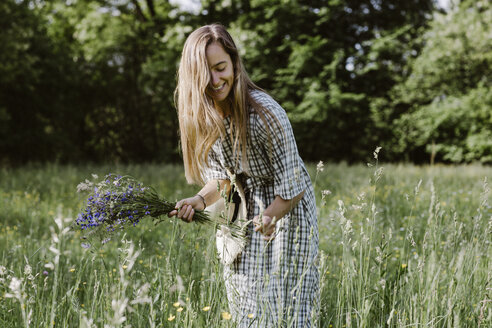 Italy, Veneto, Young woman plucking flowers and herbs in field - ALBF00414