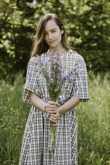 Italy, Veneto, Young woman holding bunch of wild flowers - ALBF00420