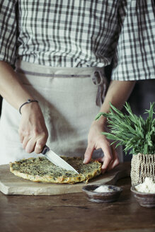 Young woman slicing homemade chickpea and herb cake - ALBF00423
