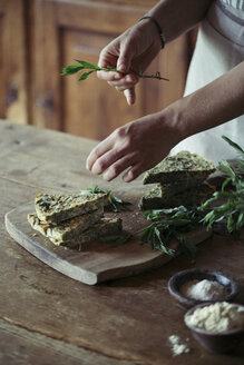 Young woman garnishing homemade chickpea and herb cake - ALBF00435