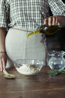 Young woman in kitchen preparing dough for fresh chickpea cake - ALBF00444