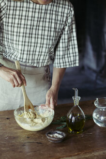 Young woman in kitchen preparing dough for fresh chickpea cake - ALBF00447