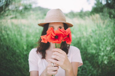 Woman holding a bouquet of red poppies in spring - GEMF02069