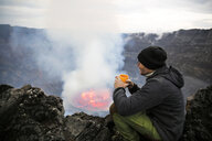 Africa, Democratic Republic of Congo, Virunga National Park, Man sittiing over Nyiragongo volcano crater - REAF00301