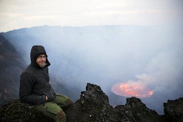 Africa, Democratic Republic of Congo, Virunga National Park, Man sittiing over Nyiragongo volcano crater - REAF00304