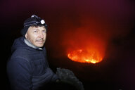 Africa, Democratic Republic of Congo, Virunga National Park, Man sittiing over Nyiragongo volcano crater - REAF00310
