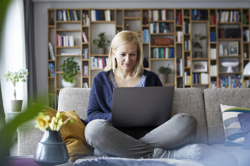 Woman at home sitting on couch using laptop - RBF06297