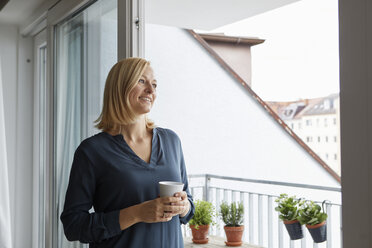 Smiling woman holding cup of coffee looking out of balcony door - RBF06300