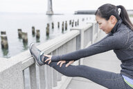 Female runner stretching on bridge, San Francisco, California - ISF09669
