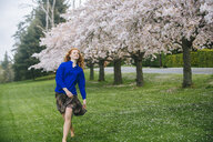 Young woman dancing barefoot in spring park - ISF09675