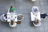 High angle view of businessmen and businesswomen having working lunch on hotel terrace - ISF09714