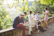 Group of friends relaxing together, sitting on wall, outdoors, eating - CUF31499