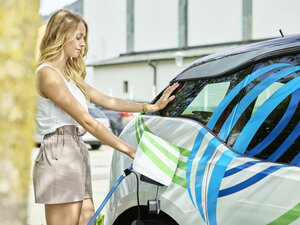 Young woman charging electric car - CVF00797
