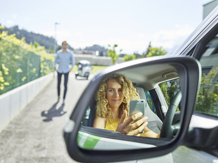 Smiling young woman using cell phone in electric car - CVF00800