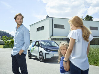 Family with electric car in front of house - CVF00803