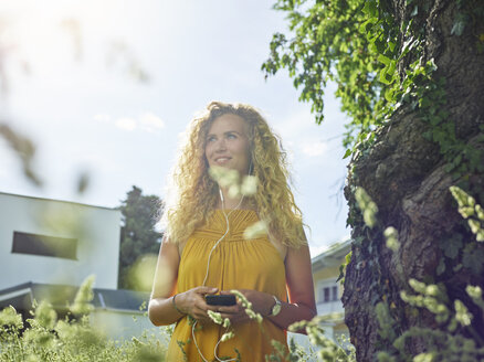 Smiling young woman with cell phone and earphones outdoors - CVF00806