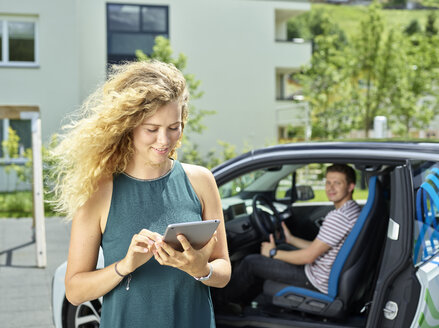 Smiling young woman using tablet with man sitting in electric car in background - CVF00809