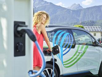 Young woman charging electric car - CVF00812