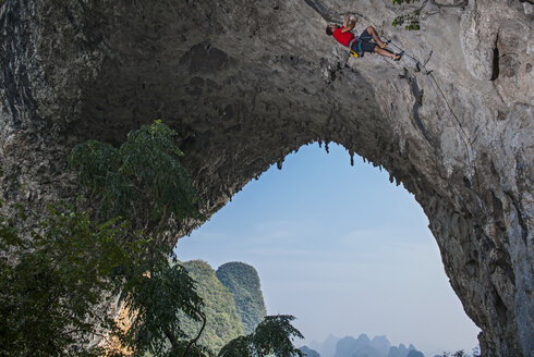 Low angle view of rock climber on Moon Hill, Yangshuo, Guangxi Zhuang, China - CUF31584
