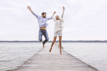 Mature couple jumping for joy on pier - CUF31608