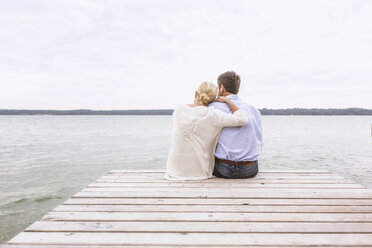 Mature couple sitting on pier, looking at view, rear view - CUF31611