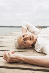 Senior woman relaxing on pier, smiling, elevated view - CUF31623