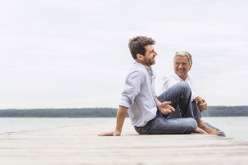 Two men sitting on pier, relaxing, smiling - CUF31632