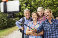 Group of friends taking self portrait, using selfie stick and smartphone - CUF31644