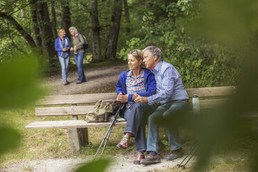 Couple sitting on bench in forest, looking at view - CUF31647