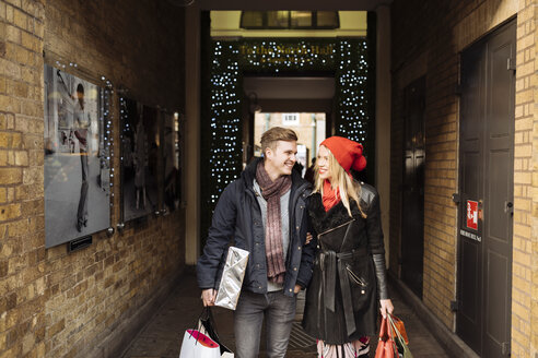 Young shopping couple strolling in alley, Covent Garden, London, UK - CUF31683