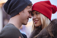 Head and shoulder shot of romantic young couple wearing knit hats - CUF31764