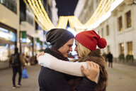 Romantic young couple hugging on street at xmas, London, UK - CUF31767