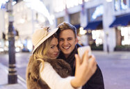 Young couple taking smartphone selfie at xmas on New Bond street, London, UK - CUF31770