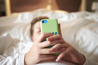 Close up of teenage boys hands holding smartphone on bed - CUF31818
