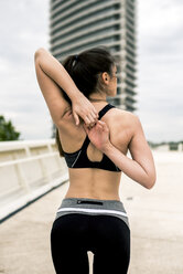 Sportive woman stretching shoulder and arm, rear view - ACPF00028