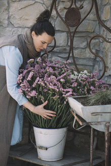 Woman arranging fresh flowers in metal bucket - ALBF00472