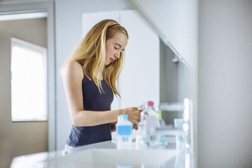 Young girl in bathroom, squeezing toothpaste onto brush - CUF31871